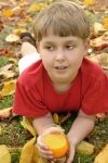 Autumn leaf fall and a boy with orange juice